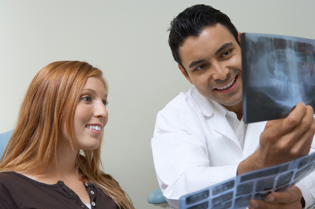 Smiling Dentist with patient x rays photo